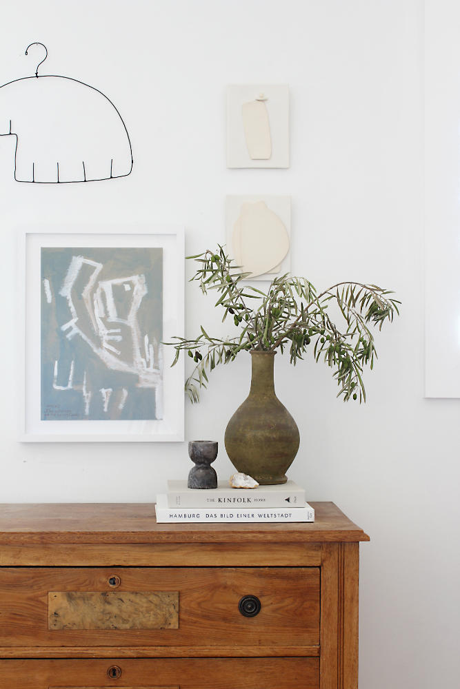 clay-vase-on-wooden-side-table-wall-art